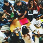 top down view of a group of students studying around a small table.
