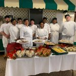 Group of culinary students posing behind a beautiful spread of food