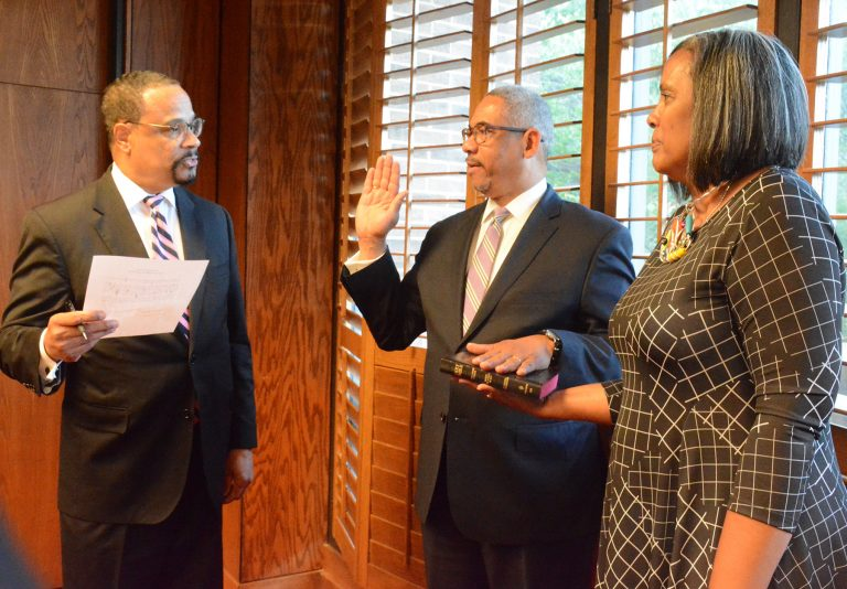 new board member being sworn in with wife.