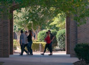students walking through main campus courtyard arches