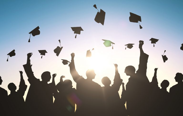 Silhouettes of many happy students in gowns throwing mortarboards in air