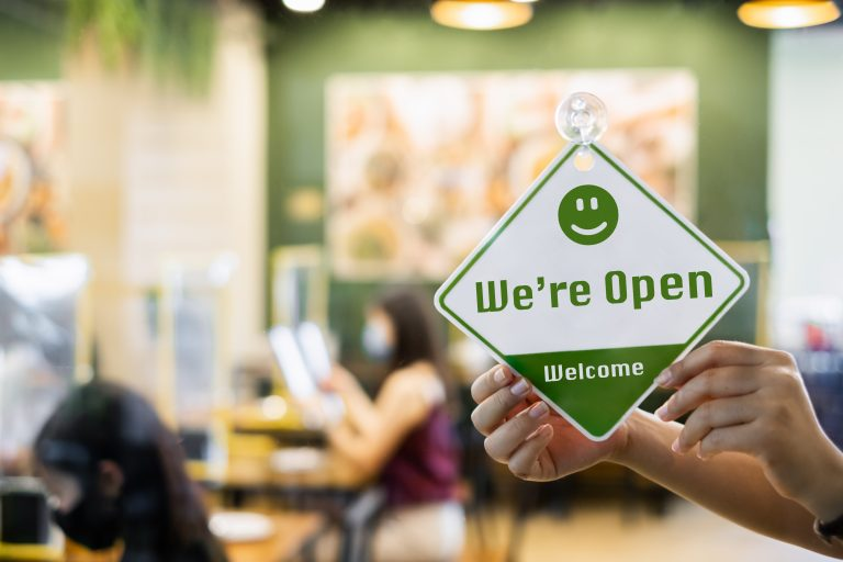 """Store front with """"We're Open Welcome"""" sign."""