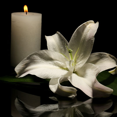 Photo of a burning candle and a flower