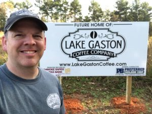 """Jason Shearin in front of sign that says """"Future Home Of: Lake Gaston Coffee Company"""