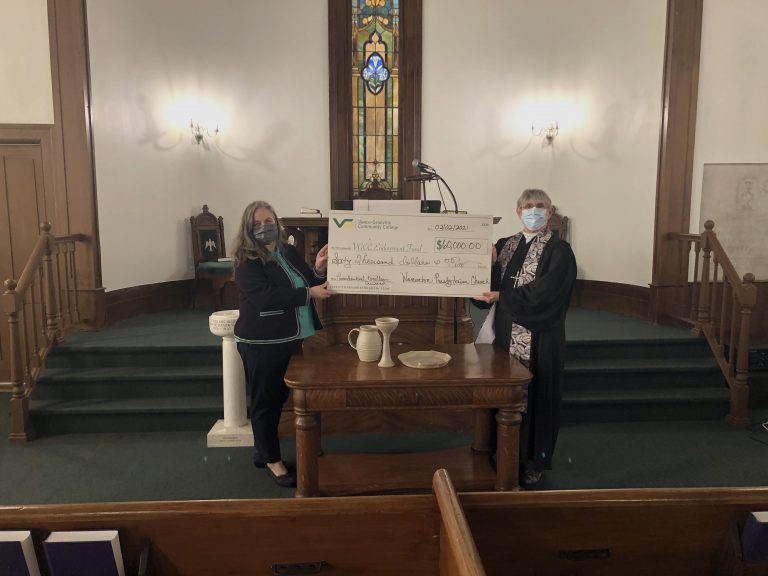Two people holding a donation check