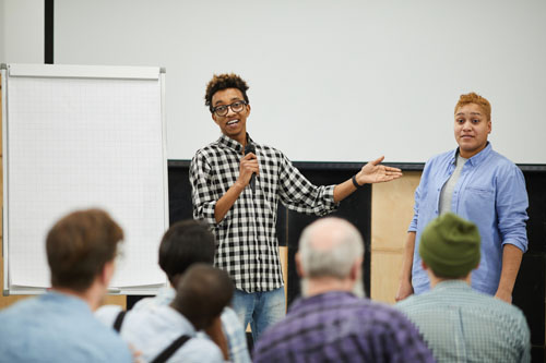 Two speakers giving a presentation to a small group