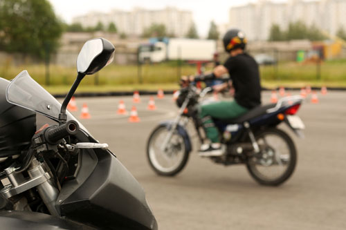 motorcycle rider in a parking lot with orange cones