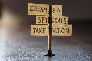 "Road sign that say ""Dream Big"", ""Set Goals"", ""Take Action"""