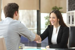 Happy women shaking hands with a male client